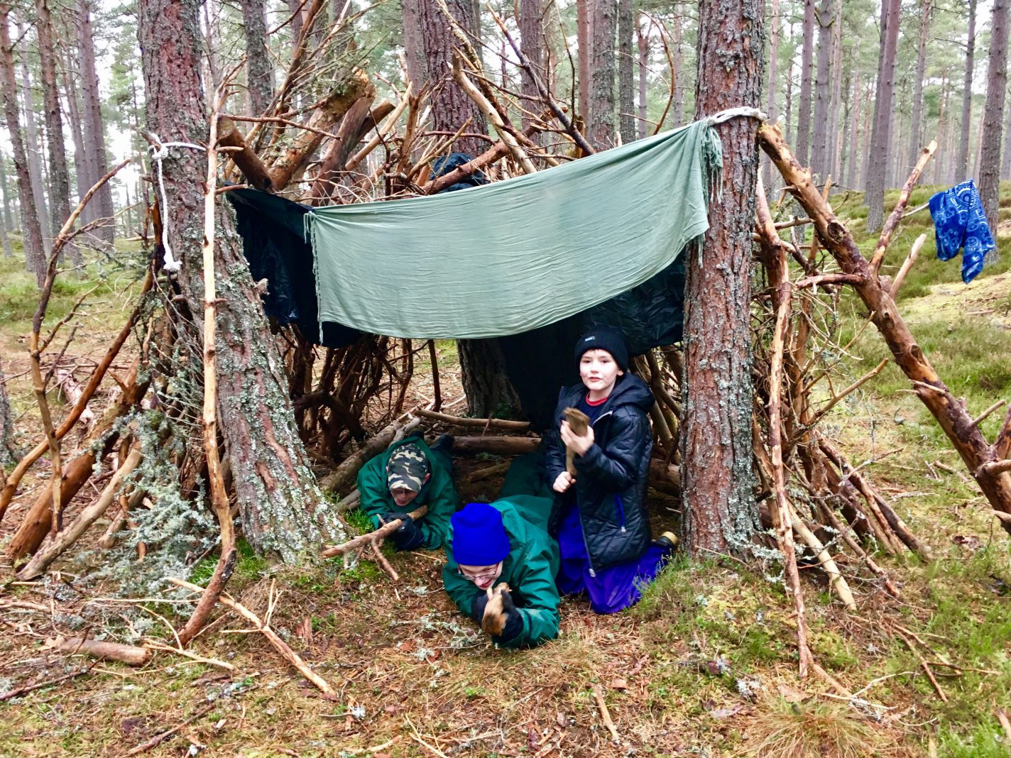Young people with disabilities building a den in the woods